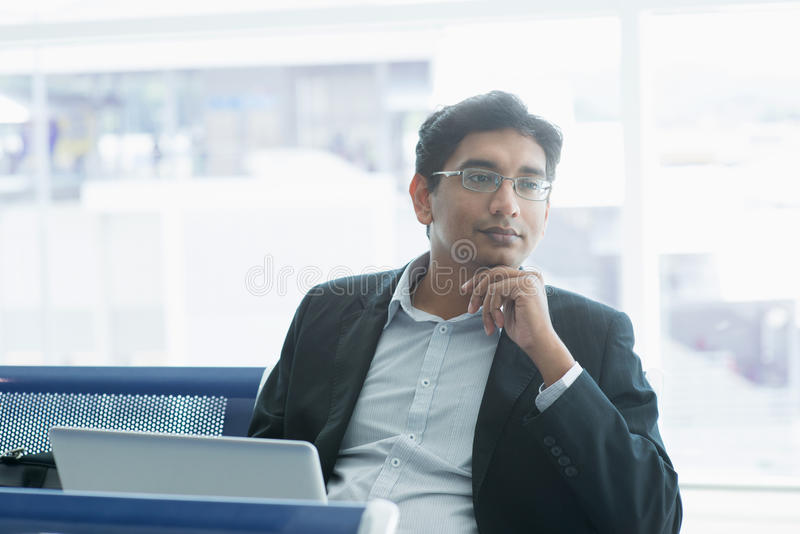 Homme indien d'affaires ayant une pensée à l'aéroport photographie stock