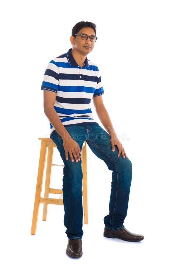 Homme indien de plein corps s'asseyant sur une chaise au-dessus du fond blanc images stock
