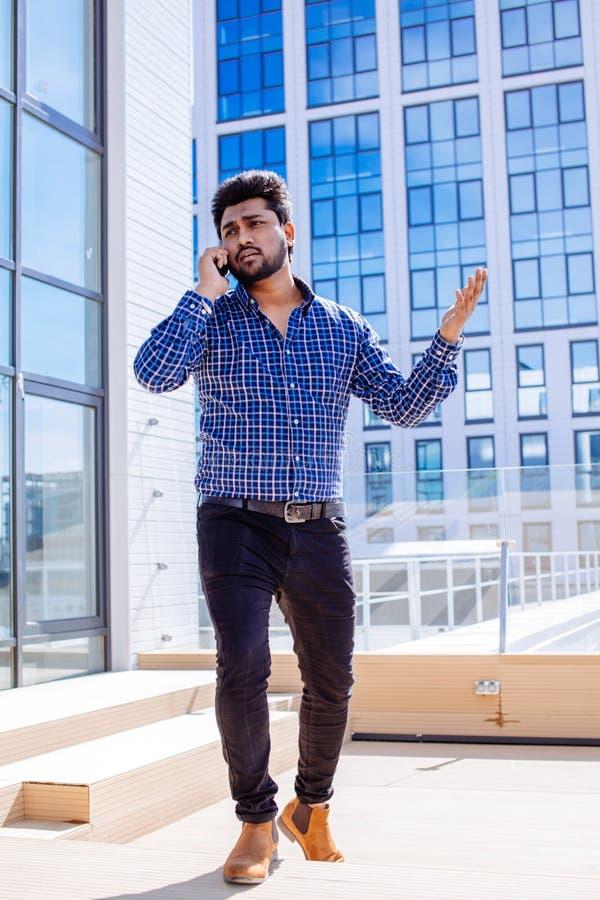 Homme indien en tissu occasionnel avec la barbe appelant devant un immeuble de bureaux photographie stock
