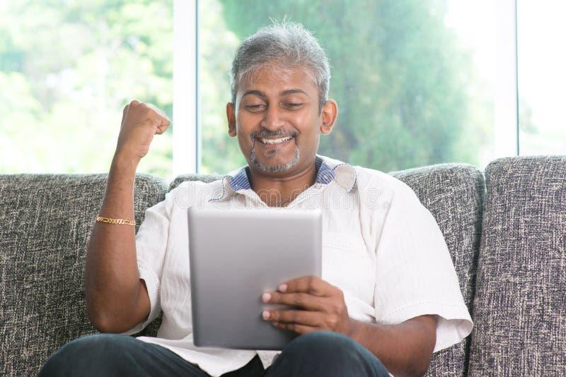 Homme indien encourageant tout en à l'aide du PC de comprimé image libre de droits