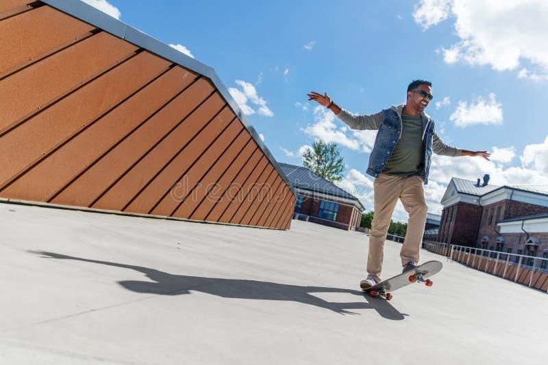 Homme indien faisant le tour sur la planche à roulettes sur le dessus de toit images libres de droits