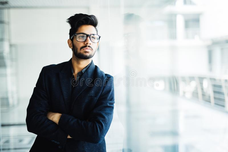 Homme indien heureux d'affaires dans le costume se tenant dans le bureau moderne photos stock