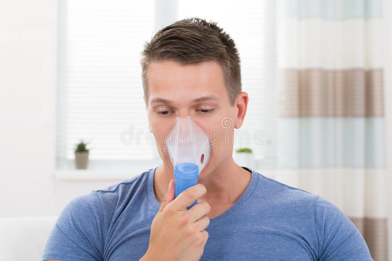 Homme inhalant par le masque d'inhalateur photographie stock