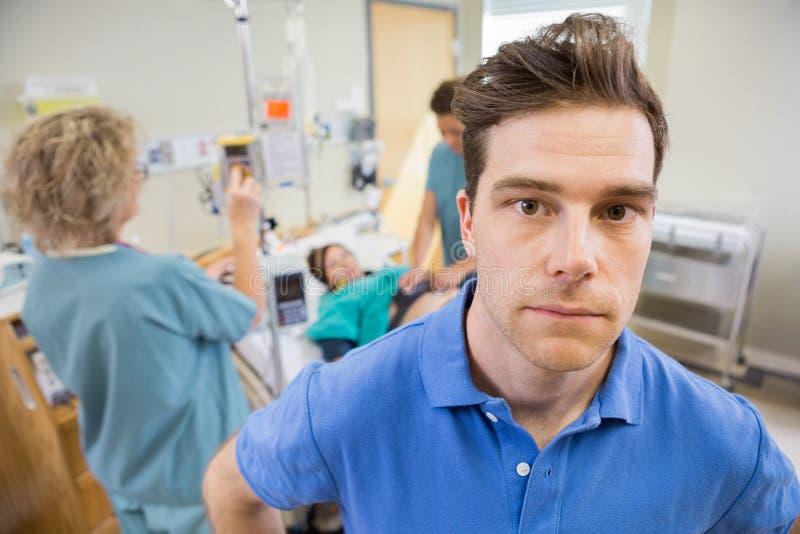 Homme inquiété avec des infirmières examinant la femme enceinte photographie stock