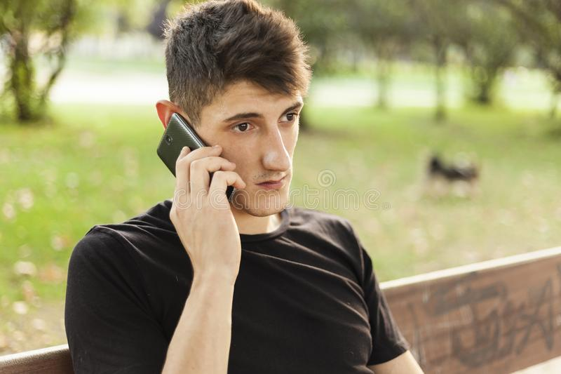 Homme inquiété parlant par le téléphone dehors photos stock