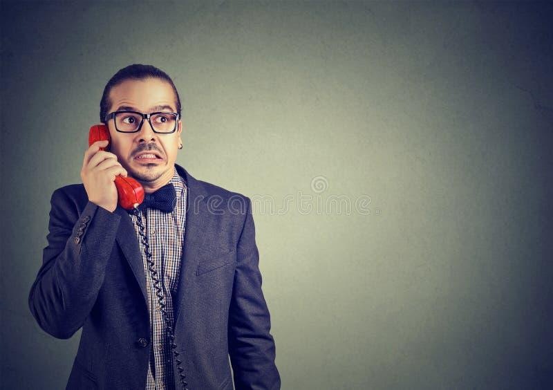 Homme inquiété recevant la mauvaise nouvelle au téléphone images libres de droits