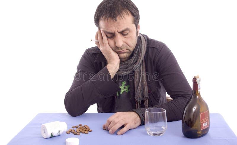 Homme inquiété s'asseyant à la table image stock