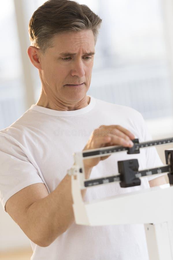 Homme inquiété vérifiant son poids sur l'échelle d'équilibre photo stock