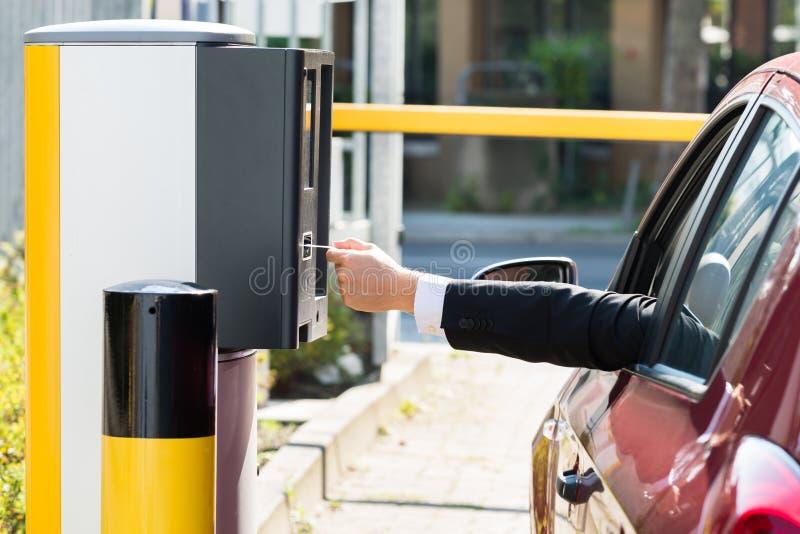 Homme insérant le billet pour l'aire de stationnement image libre de droits
