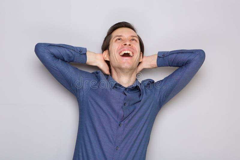Homme insouciant de tenue professionnelle décontractée avec des mains derrière rire principal photo libre de droits
