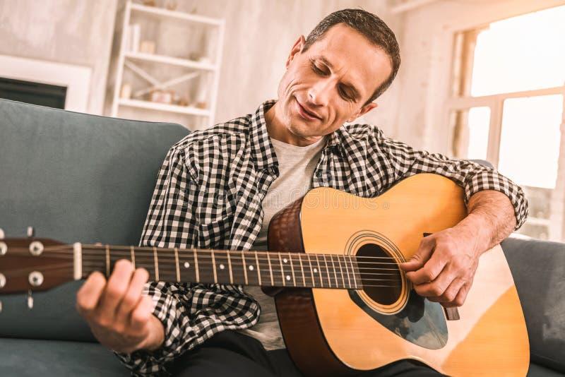 Homme inspiré focalisé jouant son instrument préféré photo libre de droits