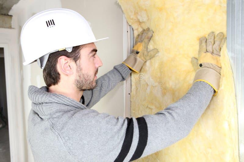 Homme installant l'isolation de mur photographie stock