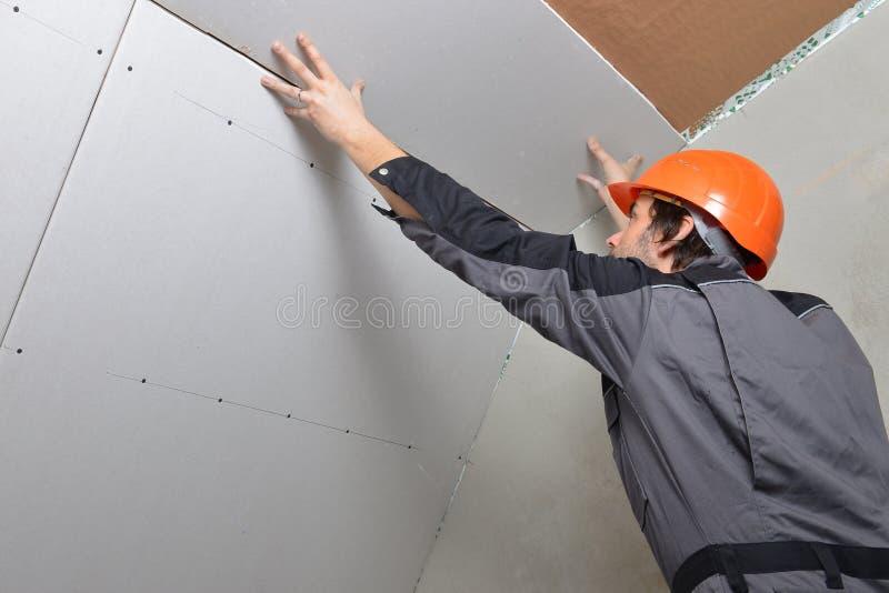 Homme installant la cloison sèche image stock