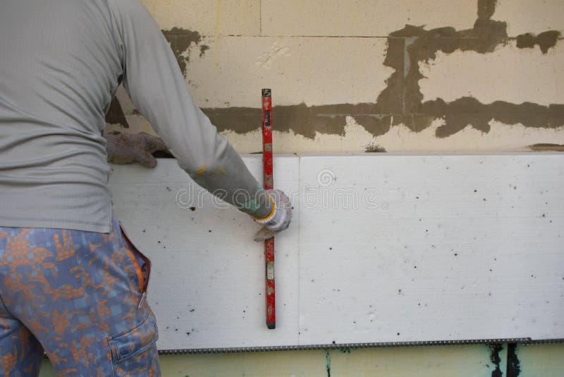 Homme installant la feuille d'isolation image stock