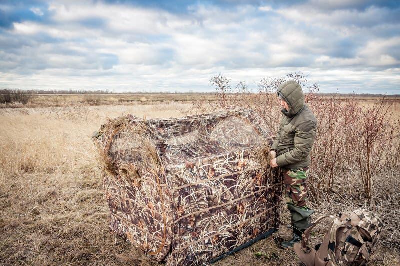 Homme installant la tente de chasse dans le domaine rural photographie stock