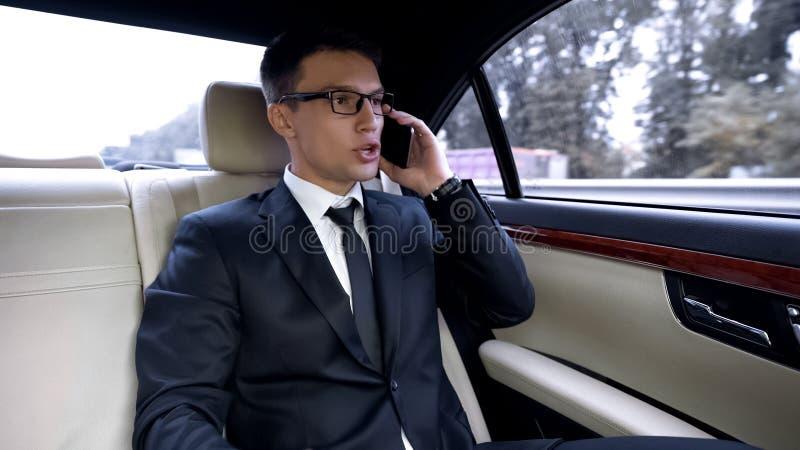 Homme irrité dans le costume criant tout en parlant au téléphone, le trafic dans la ville photos libres de droits