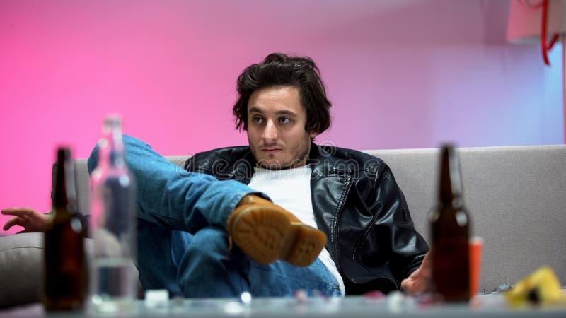Homme ivre assis sur un canapé à la maison, bouteilles de bière sur la table, toxicomanie images libres de droits