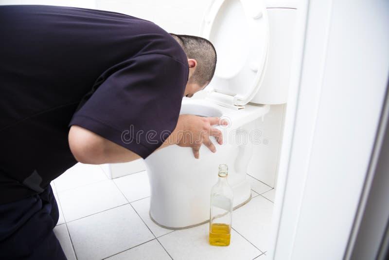 Homme ivre avec la bouteille de vin dans la toilette photo libre de droits