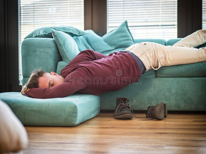 Homme ivre se reposant sur le divan avec la tête sur le plancher images libres de droits