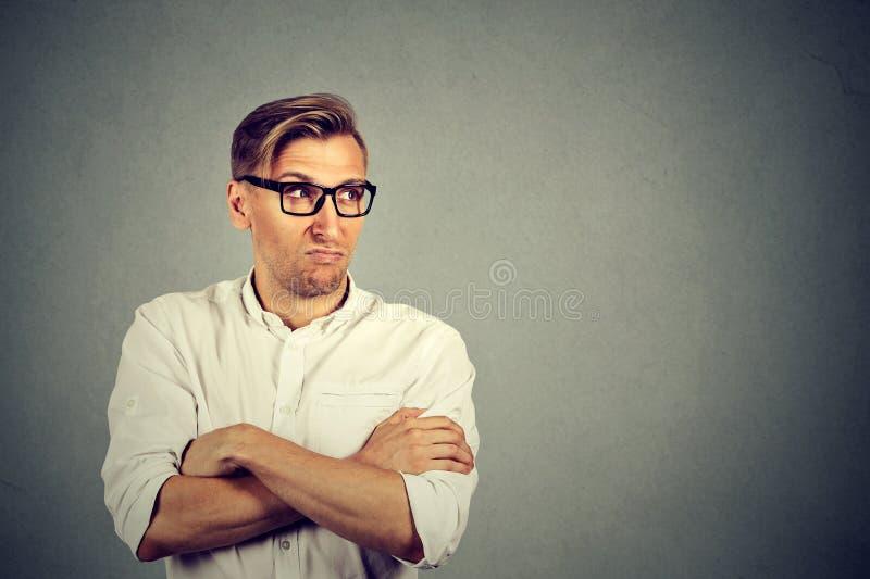 Homme jaloux regardant loin dans l'aversion photographie stock