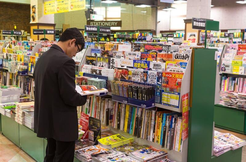 Homme japonais lisant un magazine photo stock