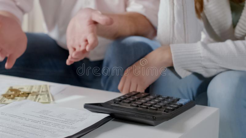 Homme jetant des mains près de l'argent, couple frustré avec le bas budget de famille images libres de droits