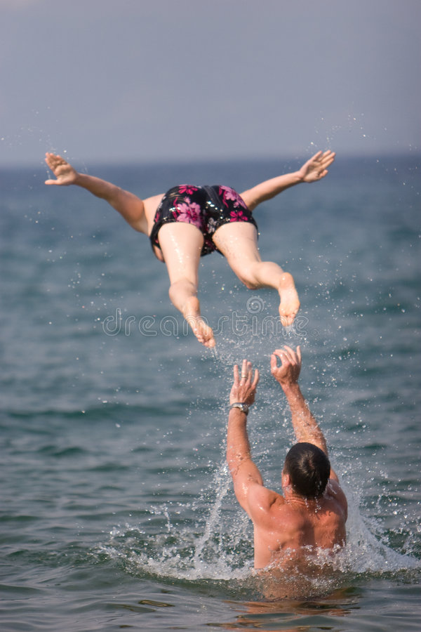 Homme jetant la femme en l'air photo stock