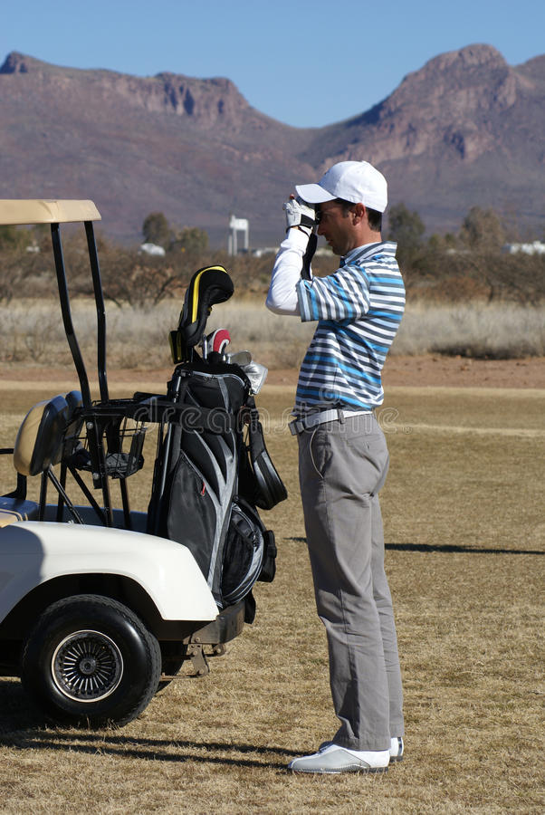 Homme jouant au golf utilisant le télémètre images stock