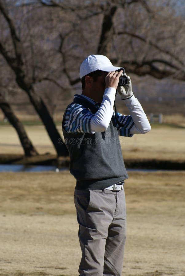 Homme jouant au golf utilisant le télémètre photographie stock libre de droits