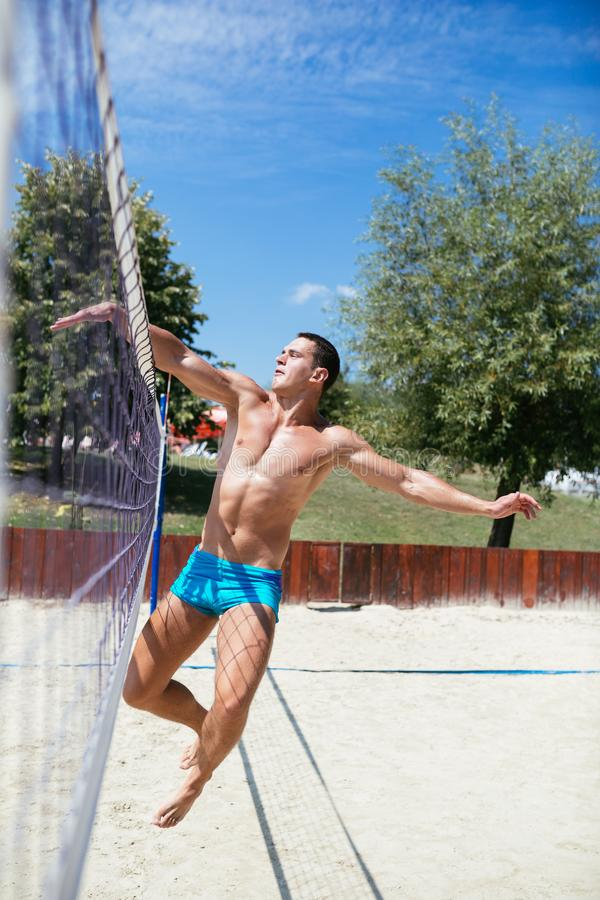 Homme jouant au volleyball de plage photo stock
