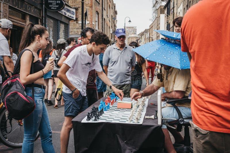 Homme jouant aux échecs avec des passants par dans la ruelle de brique, Londres, R-U photo stock