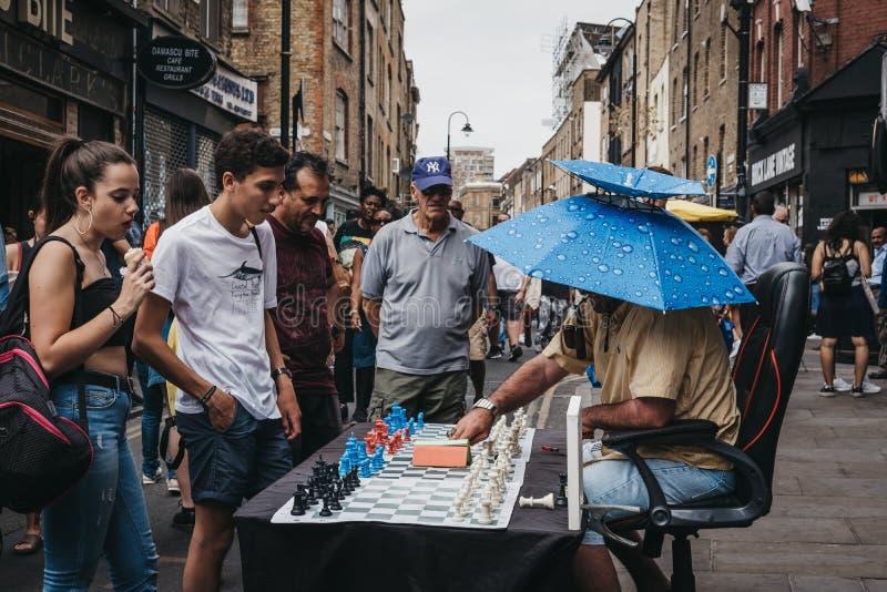 Homme jouant aux échecs avec des passants par dans la ruelle de brique, Londres, R-U photo libre de droits
