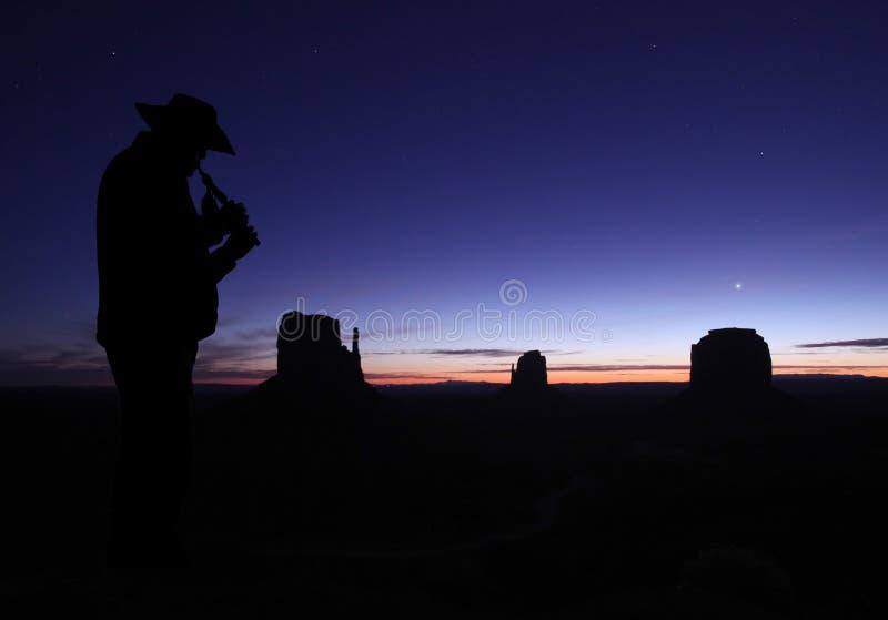 Homme jouant la cannelure dans le désert au crépuscule images libres de droits