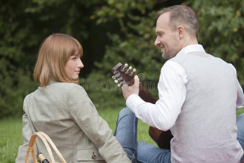 Homme jouant la guitare par pique-nique photos stock