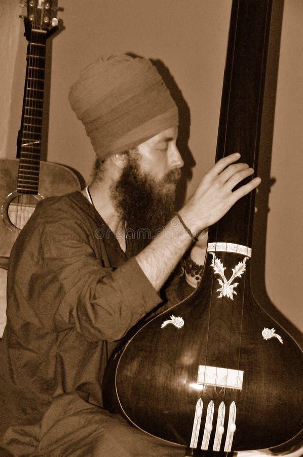 homme jouant le tambura image stock