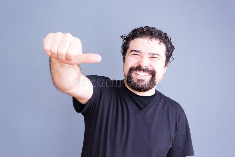 Homme joyeux faisant le geste de main latéral de pouce image stock