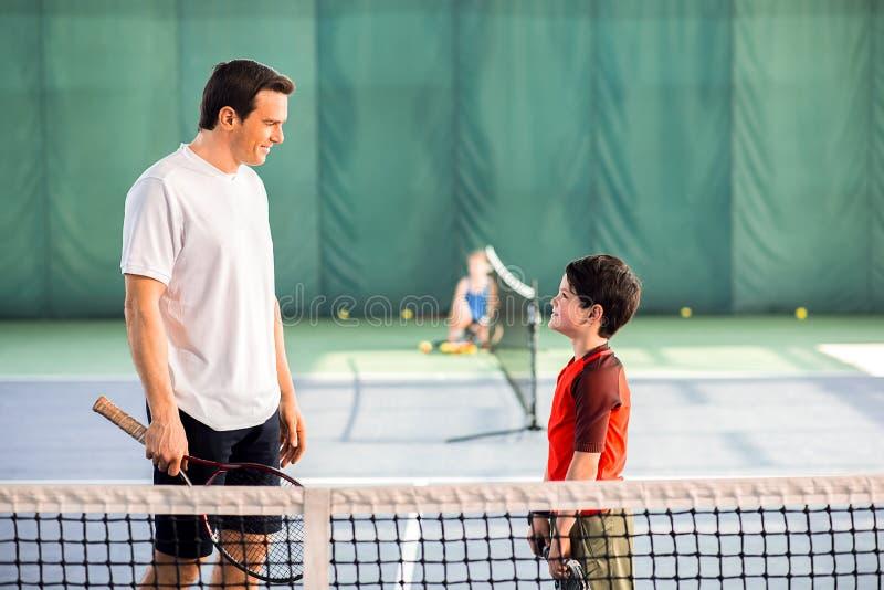 Homme joyeux jouant le tennis avec son fils photos libres de droits
