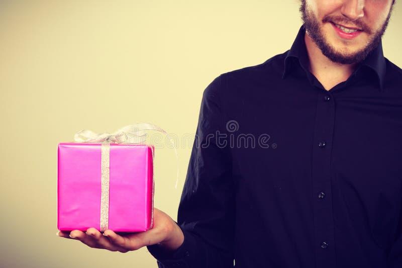 Homme jugeant le boîte-cadeau rose actuel disponible photo stock