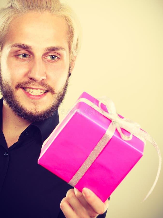 Homme jugeant le boîte-cadeau rose actuel disponible photos stock