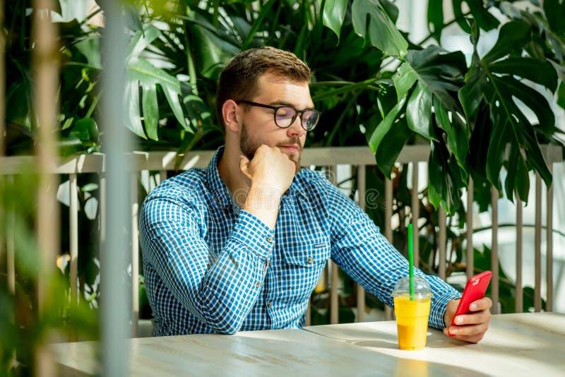 Homme ? l'aide du t?l?phone portable dans un caf? images stock