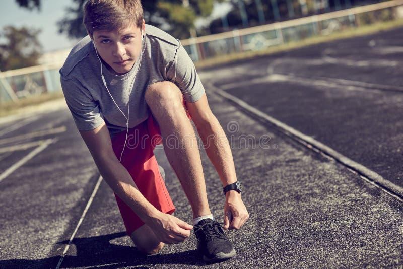 Homme laçant des chaussures de sport pour se préparer à la formation au lever de soleil image libre de droits