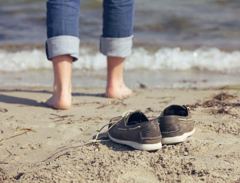 Homme laissant ses chaussures derrière sur le sable image libre de droits
