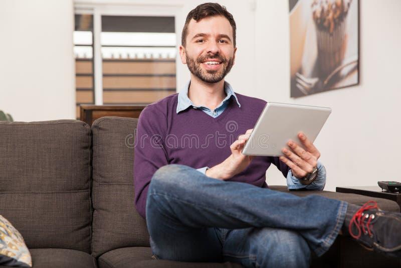 Homme latin à l'aide d'un comprimé à la maison images libres de droits