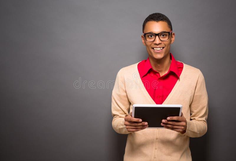 Homme latin bel avec la tablette dans le studio images stock