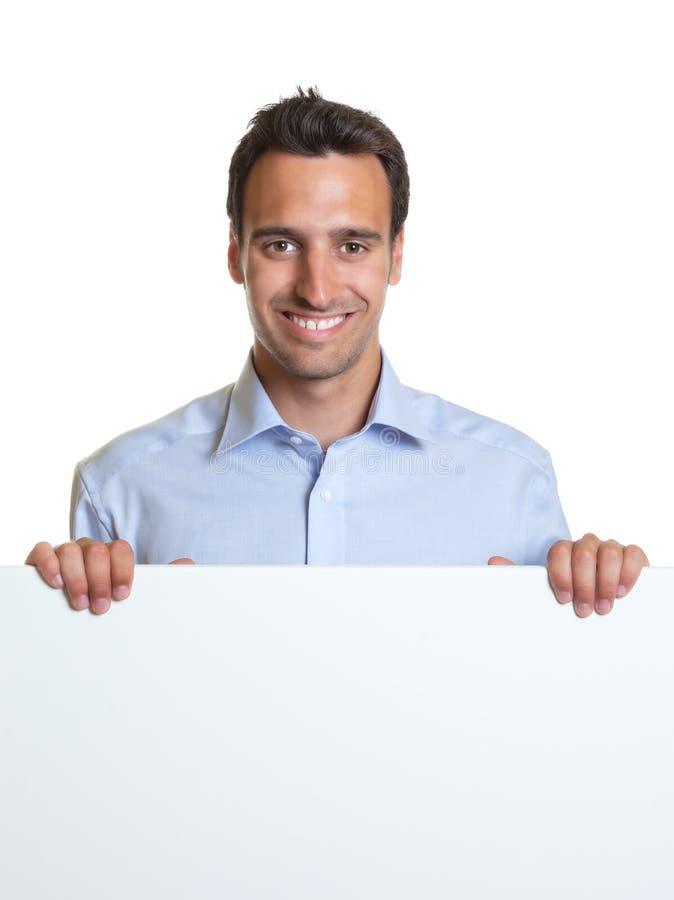 Homme latin de sourire avec une enseigne pour faire de la publicité photo libre de droits