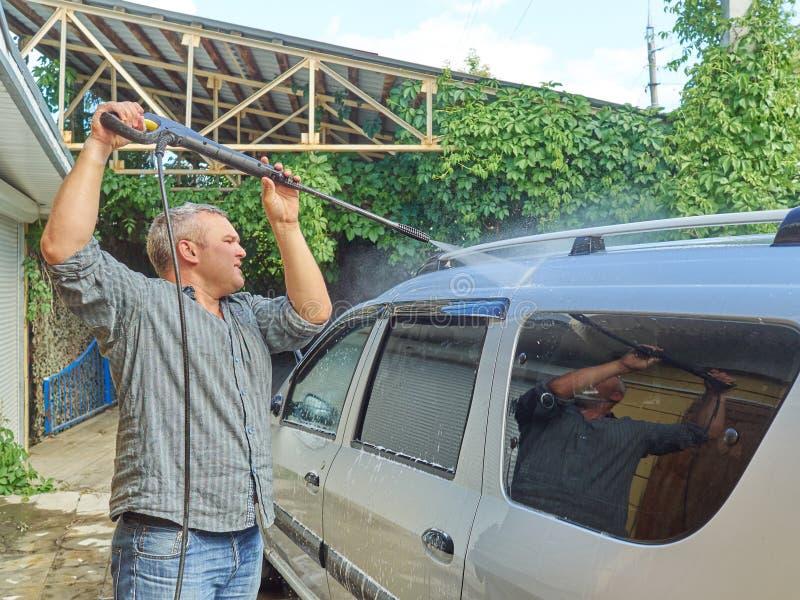 Homme lavant sa voiture argentée près de la maison photographie stock