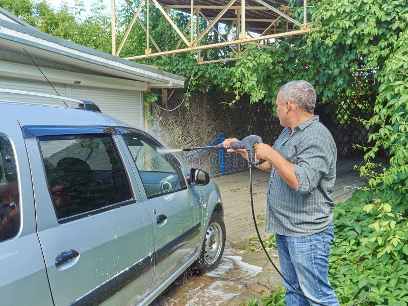 Homme lavant sa voiture argentée près de la maison photographie stock libre de droits