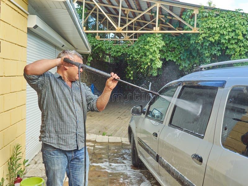 Homme lavant sa voiture argentée près de la maison photo libre de droits