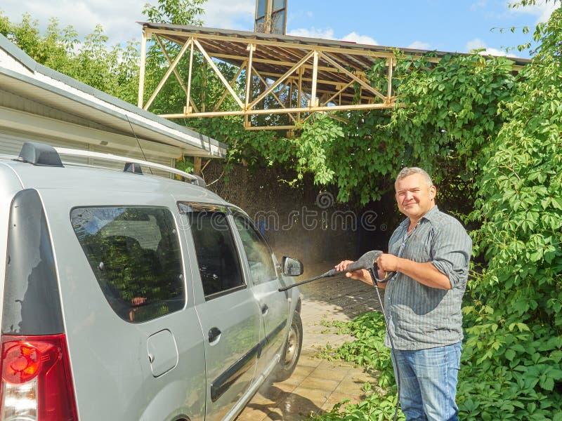 Homme lavant sa voiture argentée près de la maison photos libres de droits