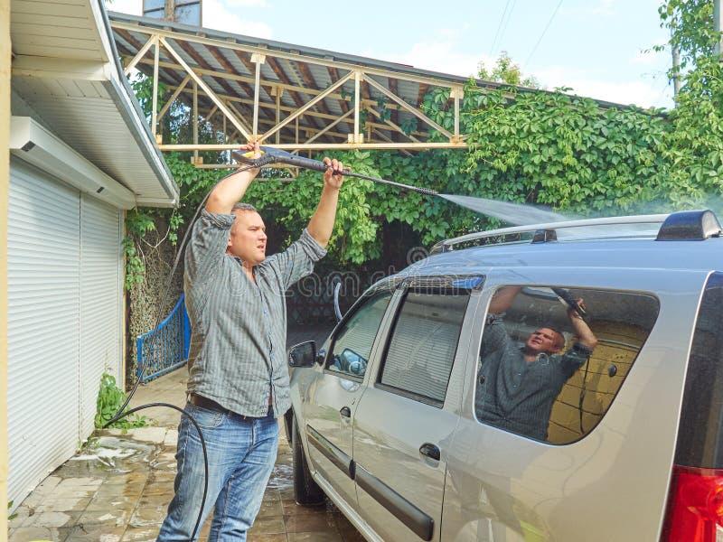 Homme lavant sa voiture argentée près de la maison image stock